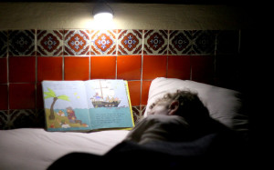 A little boy in Mexico uses his light to read by.